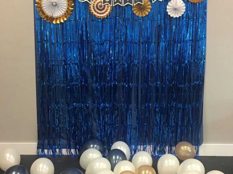Blue streamers with gold white and black balloons